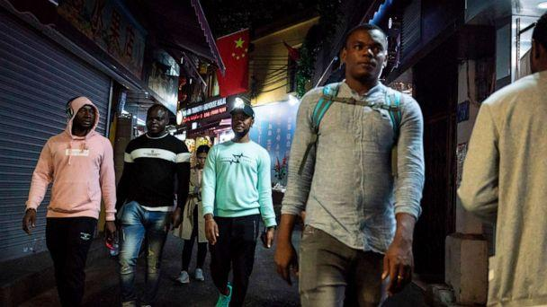 PHOTO: FILE PHOTO: People walk in the 'Little Africa' district in Guangzhou, the capital of southern China's Guangdong province, March 1, 2018. (Fred Dufour/AFP via Getty Images, File )