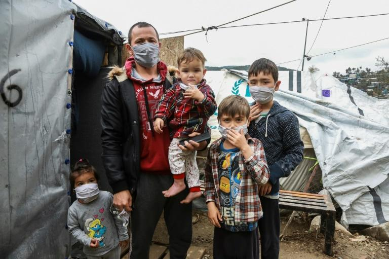 A migrant family wearing handmade protective face masks in the camp of Moria on the Greek island of Lesbos (AFP Photo/Manolis LAGOUTARIS)