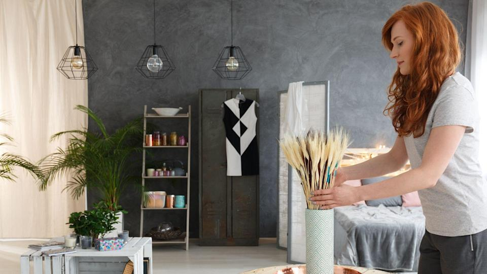 Young woman with red hair decorating contemporary fancy industrial apartment.