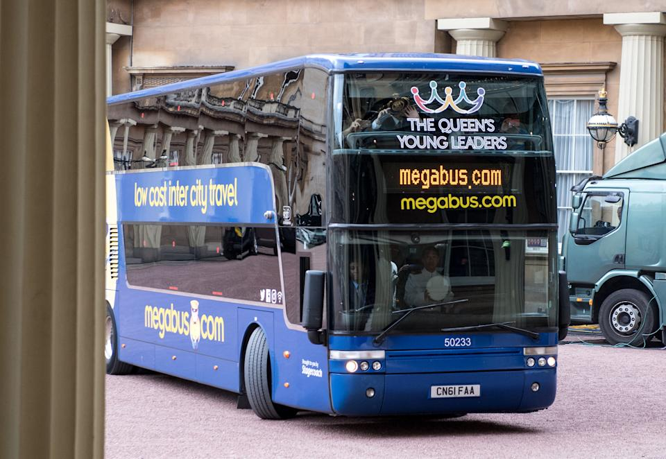 LONDON, ENGLAND - JUNE 29:  A Megabus arrives in the Quadrangle carrying this year's Queen's Young Leaders for the 2017 Queen's Young Leaders Awards Ceremony at Buckingham Palace on June 29, 2017 in London, England.  (Photo by Chris J Ratcliffe - WPA Pool/Getty Images)