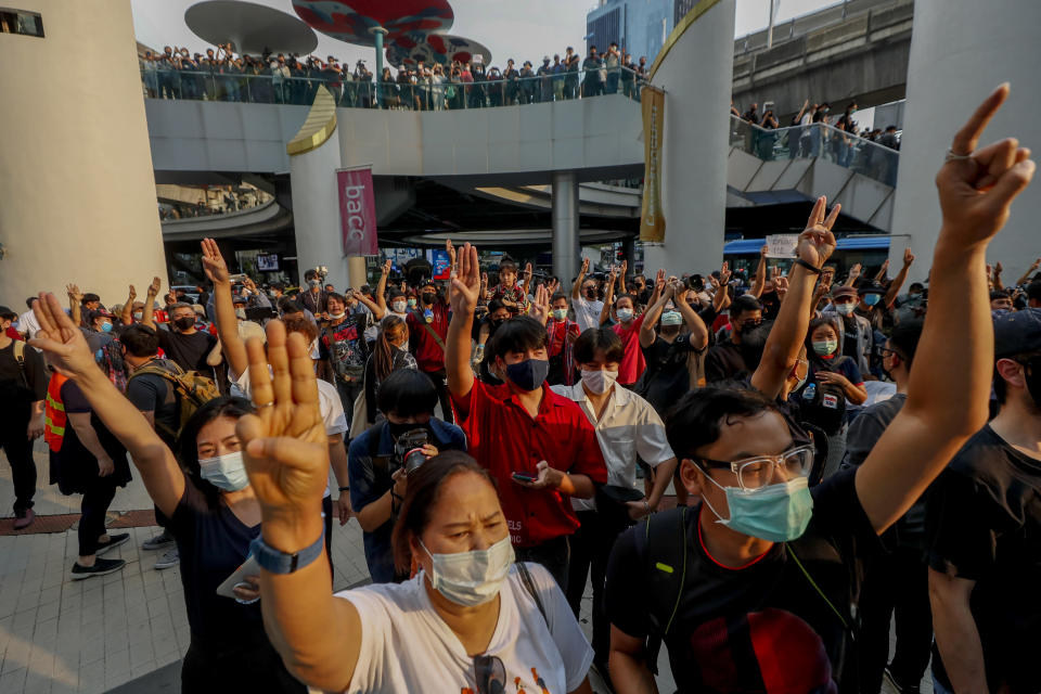 Pro-democracy protesters flash three-fingered symbol of resistance during a protest in Bangkok, Thailand, Wednesday, Feb. 10, 2021. Prosecutors in Thailand on Tuesday charged four prominent pro-democracy activists with sedition and defaming the monarchy for their protest activities. (AP Photo/Sakchai Lalit)