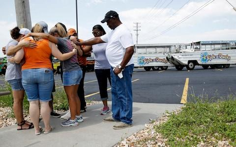 People pray outside Ride the Ducks facility in Branson, Missouri - Credit: Charlie Riedel/AP