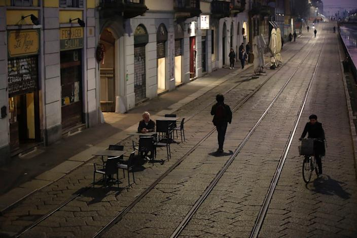 A man sits alone outside a bar at the Naviglio Grande canal in Milan, Italy, Monday, Feb. 24, 2020.
