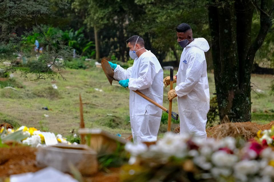 SAO PAULO, BRAZIL - JUNE 19: Bodies of Covid-19 victims are buried by officials of the Vila Formosa cemetery in Sao Paulo, Brazil, on June 19, 2021. Brazil already has almost 500,000 COVID-19 deaths and shows no signs of a slowdown in the contagion. (Photo by Marcello Zambrana/Anadolu Agency via Getty Images)