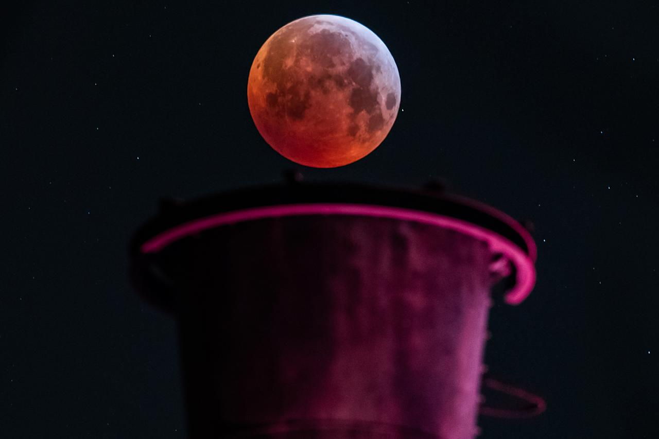<p>A picture taken on January 21, 2019 in Duisburg shows a view of the Super Blood Moon above an industrial plant during a lunar eclipse. (Photo by Marcel Kusch / dpa / AFP) </p>