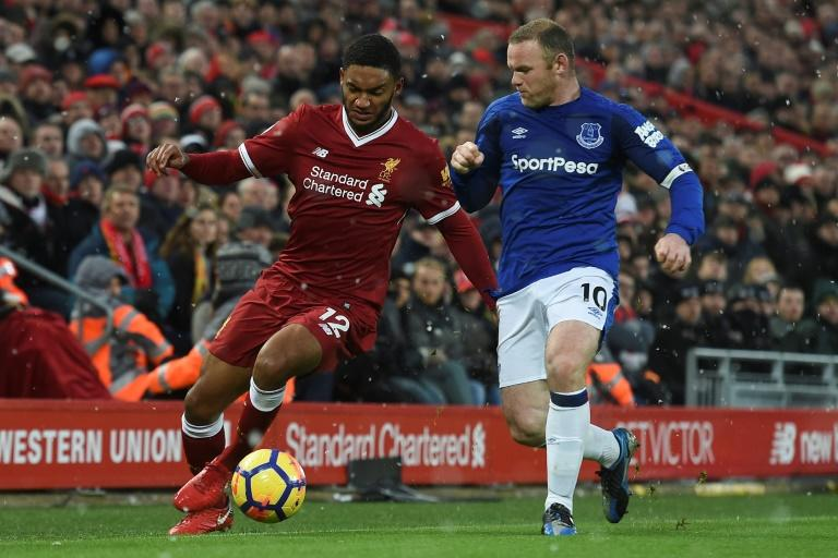 Liverpool defender Joe Gomez (L) takes on Everton striker Wayne Rooney during a match at Anfield in Liverpool on December 10, 2017