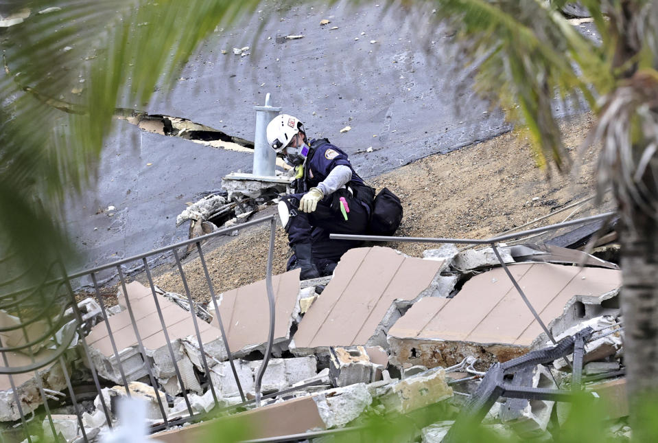 Search and rescue personnel search for survivors through the rubble at the Champlain Towers South Condo in Surfside, Fla., Friday, June 25, 2021. The apartment building partially collapsed on Thursday, June 24. (David Santiago/Miami Herald via AP)