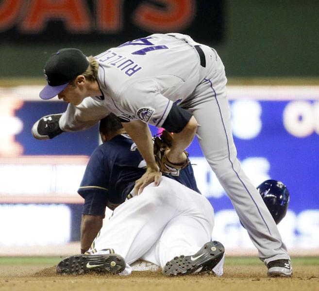 Milwaukee Brewers' Carlos Gomez gets tangled with Colorado Rockies' Josh Rutledge (14) as he is caught stealing second during the eighth inning of a baseball game Friday, June 27, 2014, in Milwaukee. (AP Photo/Morry Gash)