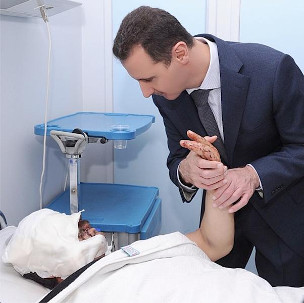This undated photo posted on the official Instagram account of the Syrian Presidency and purports to show Bashar Assad visiting a patient at a military hospital in Damascus, Syria in 2012. Amid the carnage from the Syrian civil war, President Bashar Assad has embraced every tool at his disposal including social media to project confidence and transmit his message to dedicated fans, most recently on the popular photo-sharing service Instagram posting pictures of himself and his glamorous wife surrounded by idolizing crowds.(AP Photo/Syrian Presidency via Instagram)