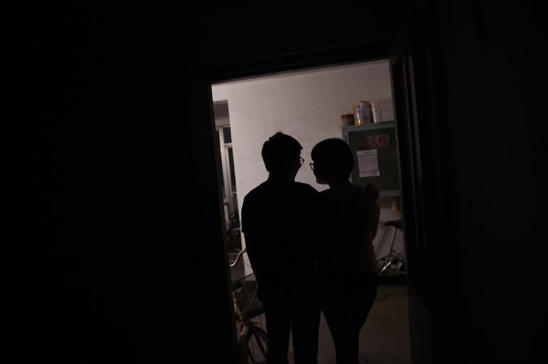 Aygul (R), an ethnic Uighur, and her ethnic Han husband Xiaohe stand in the doorway to their apartment in Beijing, May 19, 2015