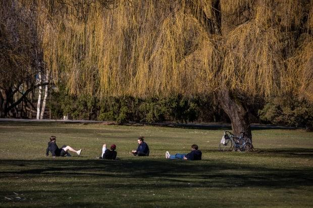 People sit in a field at a distance in Vancouver last March.