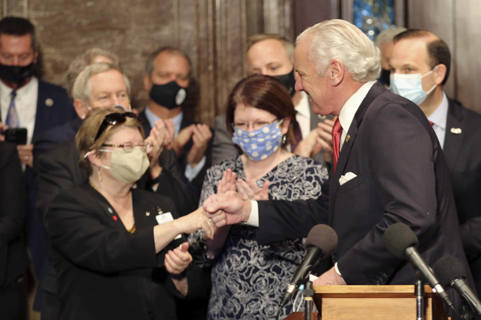 """South Carolina Gov. Henry McMaster, right, fist bumps South Carolina Citizens for Life Executive Director Holly Gatling, left, before McMaster signed a bill banning almost all abortions in the state on Thursday, Feb. 18, 2021, in Columbia, S.C. On the same day, Planned Parenthood filed a federal lawsuit to stop the measure from going into effect. The state House approved the """"South Carolina Fetal Heartbeat and Protection from Abortion Act"""" on a 79-35 vote Wednesday and gave it a final procedural vote Thursday before sending it to McMaster. (AP Photo/Jeffrey Collins)"""