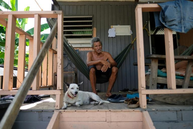 Sixto Marrero sits on the porch of his home in Puerto Rico, two years after its roof was ripped off by Hurricane Maria (AFP Photo/Ricardo ARDUENGO)