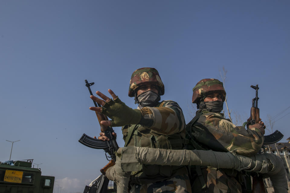 Indian army soldiers stand guard on their armored vehicle as they leave the site of a gun battle on the outskirts of Srinagar, Indian controlled Kashmir, Wednesday, Dec. 30, 2020. A gun battle between rebels and government forces overnight killed three rebels on the outskirts of Srinagar on Wednesday, officials said. (AP Photo/ Dar Yasin)