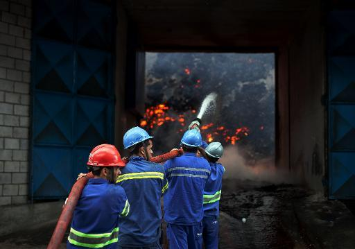 <p>Firefighters attempt to extinguish a fire in a warehouse with sugar at the Brazilian port of Santos, the biggest of Latin America on October 18, 2013</p>