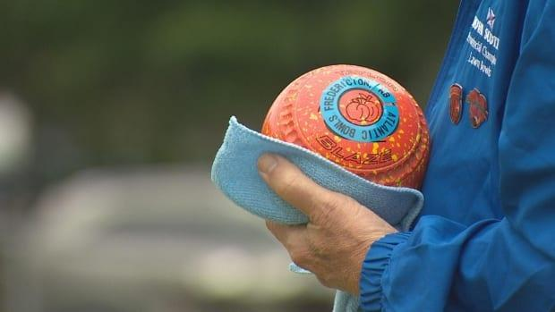 A lawn bowler from Nova Scotia stands on the green of the Atlantic Bowls tournament, which wrapped up in Fredericton on Sunday.  (Ed Hunter - image credit)