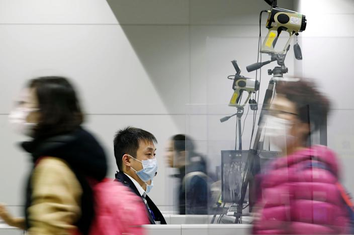 Passengers wearing masks walk by as a quarantine officer, center, monitors a thermography during a quarantine inspection at Kansai international airport in Osaka, western Japan, Wednesday, Jan. 22, 2020. Chinese health authorities urged people in the city of Wuhan to avoid crowds and public gatherings after warning on Wednesday that a new viral illness infecting hundreds of people in the country. Japan, South Korea, the United States and Taiwan have all reported one case each. All of the illnesses were of people from Wuhan or who recently had traveled there. (Kota Endo/Kyodo News via AP)