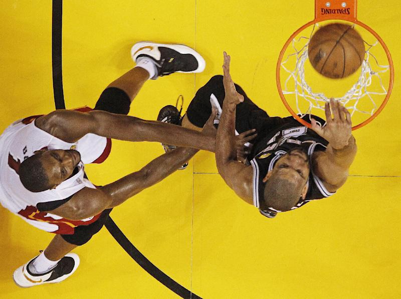 San Antonio Spurs point guard Tony Parker (9) dunks the ball over Miami Heat center Chris Bosh (1) during the second half of Game 2 in the NBA Finals basketball game, Sunday, June 9, 2013 in Miami. The Miami Heat won 103-84. (AP Photo/Mike Segar, Pool)