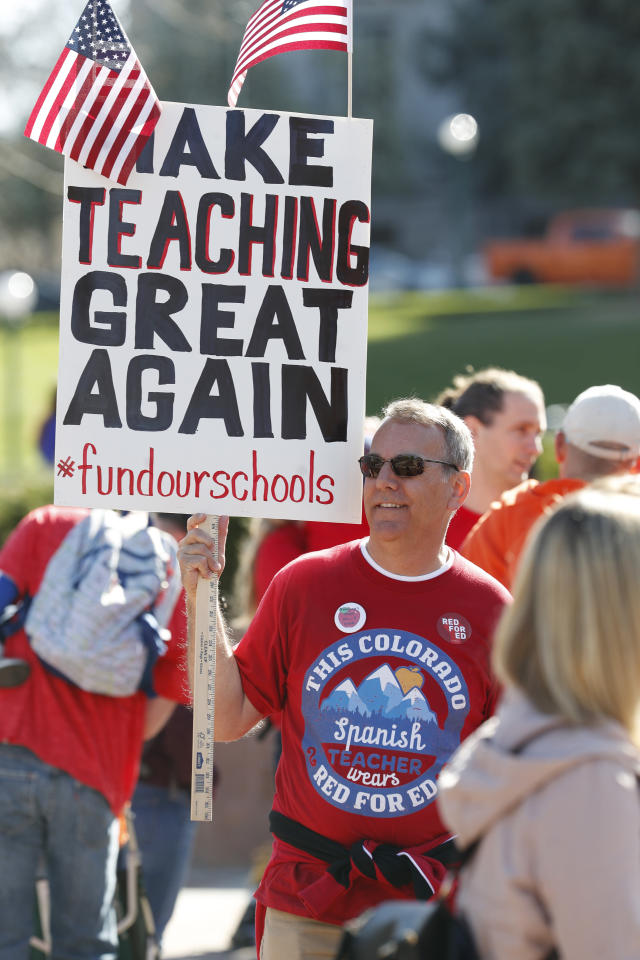 <p>Bob Roy, a teacher in Longmont, Colo., holds a placard during a teacher rally Friday, April 27, 2018, in Denver, Colo. (Photo: David Zalubowski/AP) </p>