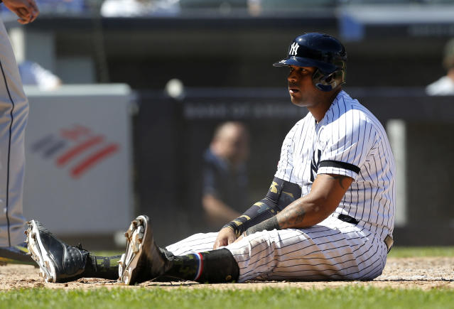 New York Yankees' Aaron Hicks sits at home plate after he was thrown out trying to score a run against the Tampa Bay Rays ending the sixth inning of a baseball game, Saturday, May 18, 2019, in New York. Hicks tried to score from second base after a base hit by Gleyber Torres. (AP Photo/Jim McIsaac)