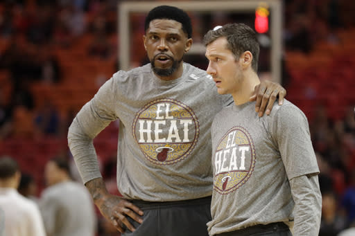 Miami Heat forward Udonis Haslem, left, and guard Goran Dragic talk before the start of an NBA basketball game against the Orlando Magic, Wednesday, March 4, 2020, in Miami. (AP Photo/Wilfredo Lee)