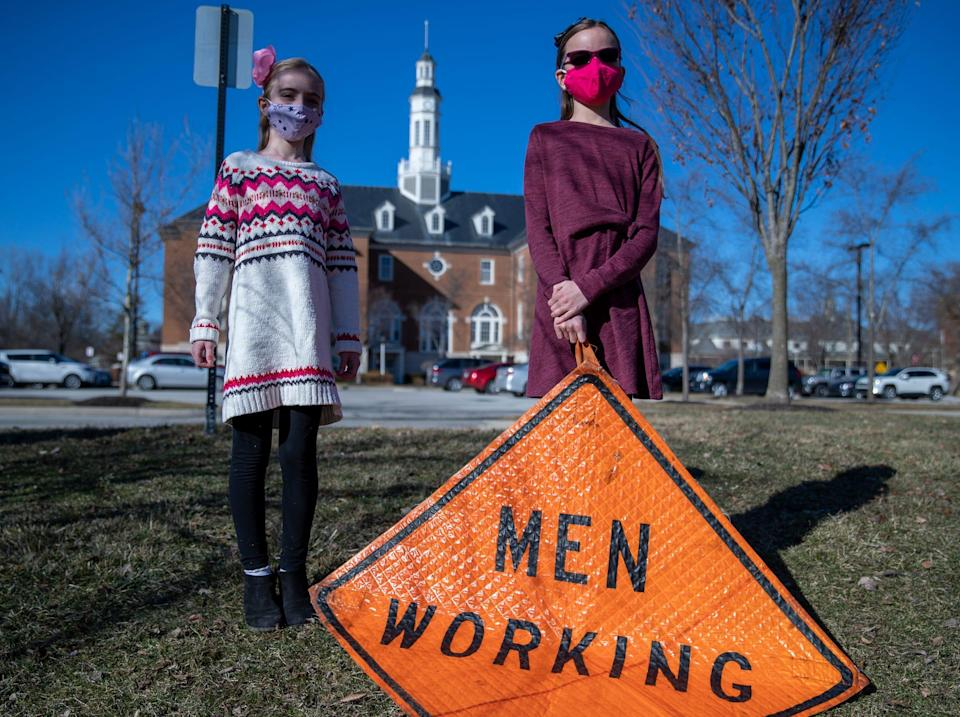 Brienne Babione (left), 9, stands with her sister Blair Babione, 11, in front of Carmel City Hall on Tuesday, March 2, 2021, a day after the girls visited a council meeting hoping to convince the city to abandon the gendered signage it uses, like the one they're holding.