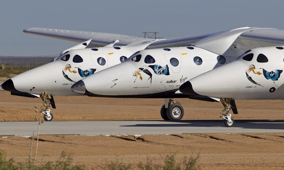 The spacecraft SpaceShipTwo, center, carried by cargo aircraft WhiteKnightTwo, is seen in front of the San Andreas Mountains heading to the hangar after a test flight outside the new Spaceport America hangar.