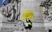 A protestor in a yellow vest sits under a banner which reads 'revolution' at the Place de Republique, during a yellow vest demonstration in Paris, Saturday, April 20, 2019. French yellow vest protesters are marching anew to remind the government that rebuilding the fire-ravaged Notre Dame Cathedral isn't the only problem the nation needs to solve. (AP Photo/Michel Euler)