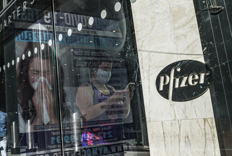 FILE - In this Nov. 9, 2020, file photo, an ad for COVID-19 testing reflects on glass at a bus stop, as pedestrians walk past Pfizer world headquarters in New York. Pfizer and BioNTech say they've won permission Wednesday, Dec. 2, 2020, for emergency use of their COVID-19 vaccine in Britain, the world's first coronavirus shot that's backed by rigorous science -- and a major step toward eventually ending the pandemic. (AP Photo/Bebeto Matthews, File)