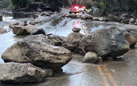 Boulders block a road after being moved by the mudslide - Credit: Reuters
