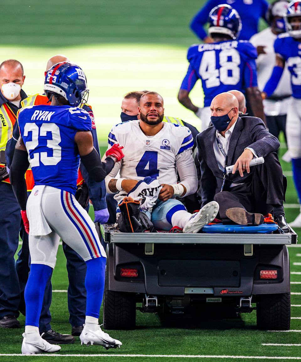 Dallas Cowboys quarterback Dak Prescott (4) is carted off the field after suffering a severe right leg injury while being tackled by New York Giants cornerback Logan Ryan (23) during an NFL football game, Sunday, Oct. 11, 2020, in Arlington, Texas.