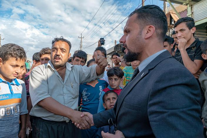 Abdullah shakes hands with Fizza Ali as a crowd gathers to hear a debate between the candidate and his prospective voters. (Photo: Shawn Carrié for Yahoo News)