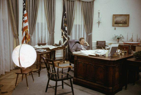 <p>President Kennedy reclines behind his desk in the Oval Office while speaking on the phone. </p>
