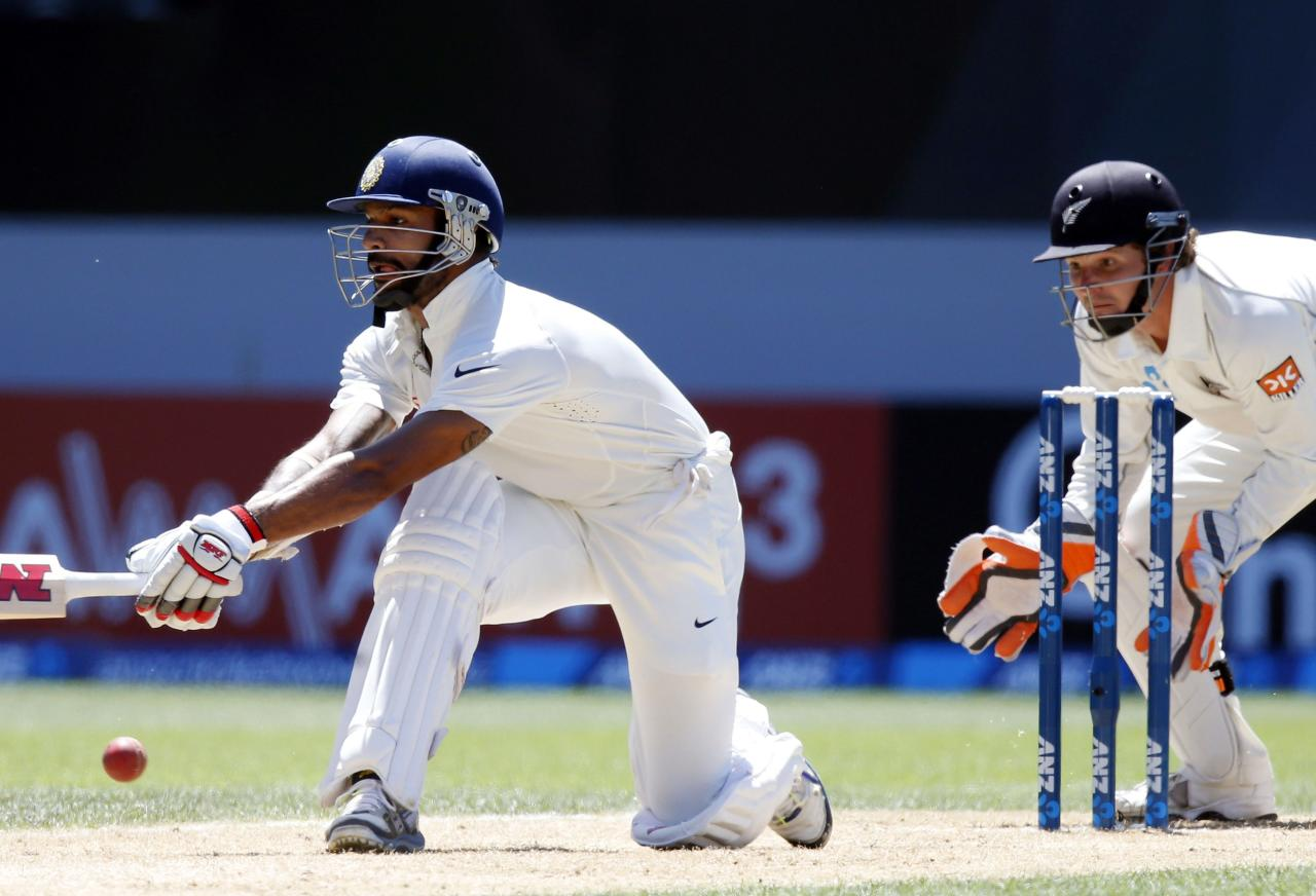 India's Shikhar Dhawan hits a reverse sweep watched by New Zealand's BJ Watling on his way to scoring a century during his second innings on day four of the first international test cricket match at Eden Park in Auckland, February 9, 2014. REUTERS/Nigel Marple (NEW ZEALAND - Tags: SPORT CRICKET)