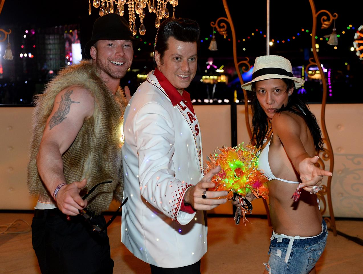 LAS VEGAS, NV - JUNE 23: Elvis Presley impersonator Brian Mills (C) poses for pictures with Jordan Bredin (L) and Jaime Doucet (R) of Canada after Mills performed their wedding ceremony at the 17th annual Electric Daisy Carnival at Las Vegas Motor Speedway on June 23, 2013 in Las Vegas, Nevada. (Photo by Ethan Miller/Getty Images)