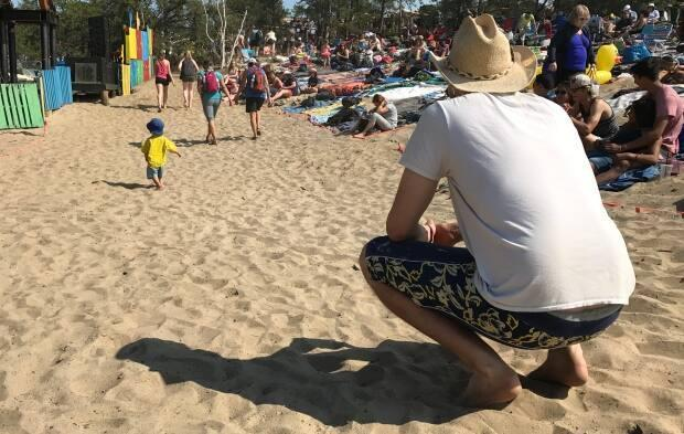 A dad keeps a close eye on his son walking on the sand at the main stage in the early afternoon sun at Folk on the Rocks in 2017.