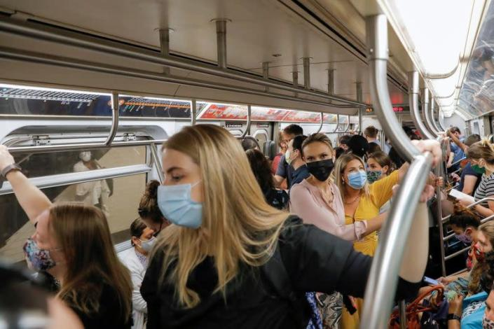 People wear masks while riding on the subway as cases of the infectious coronavirus Delta variant continue to rise in New York City, New York
