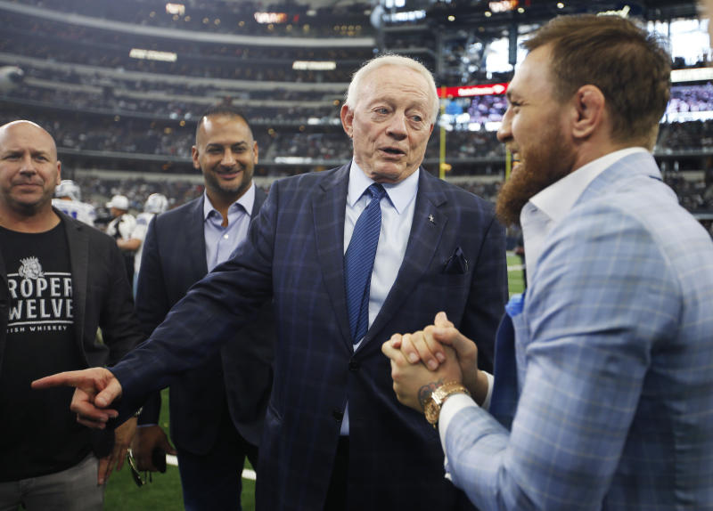 Dallas Cowboys owner Jerry Jones, second from right, and UFC fighter Conor McGregor, right, stand on the sideline before an NFL football game against the Jacksonville Jaguars in Arlington, Texas, Sunday, Oct. 14, 2018. (AP Photo/Jim Cowsert)