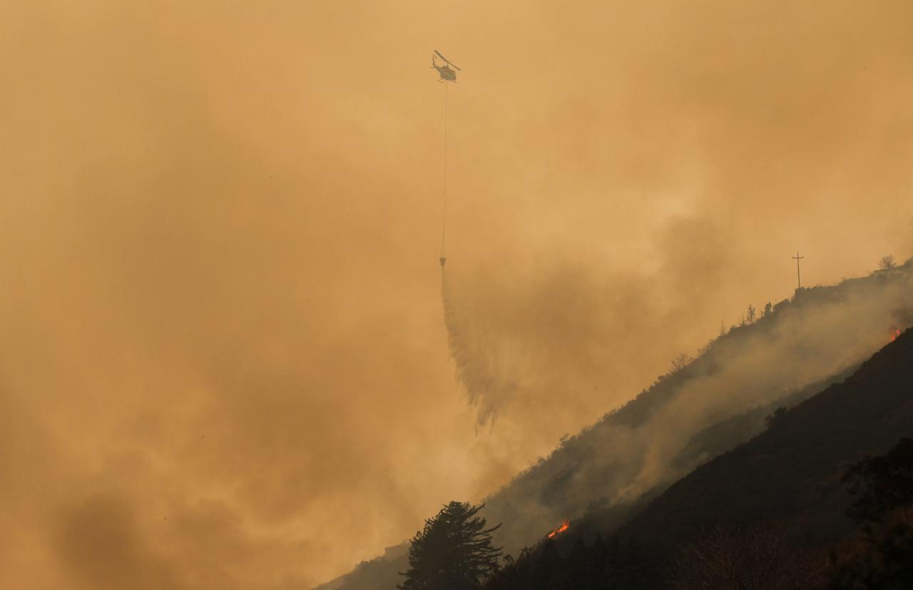 A helicopter drops ocean water on a wildfire burning on Pfeiffer Ridge in Big Sur, California, December 17, 2013. Crews battling the wildfire along central California's scenic Big Sur coastline were on guard against a possible shift in winds on Tuesday, after the blaze destroyed at least 15 dwellings and forced 100 people to flee their homes, fire and county officials said. REUTERS/Michael Fiala (UNITED STATES - Tags: ENVIRONMENT DISASTER TRANSPORT)