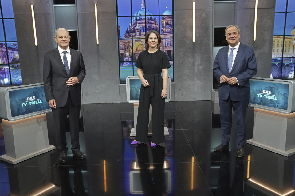 Olaf Scholz, candidate for chancellor of the SPD and Federal Minister of Finance, left, Annalena Baerbock, German Green Party co-leader and candidate for chancellor, center, and Armin Laschet, candidate for chancellor of the CDU/CSU and chairman of the CDU, right, stand together before the start of the third TV debate in Berlin, Sunday Sept. 19, 2021. (Kay Nietfeld/dpa via AP)