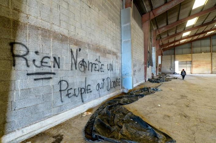 """Graffiti reading """"nothing can stop people dancing"""" inside one of the hangars"""