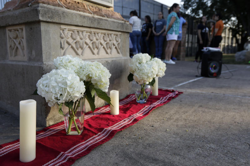 An altar of candles and white hydrangea flowers stands in memoriam of the 22 victims of the recent El Paso shooting during a vigil Sunday, Aug. 11, 2019, at Alice Wilson Hope Park in Brownsville, Texas.(Denise Cathey/The Brownsville Herald via AP)