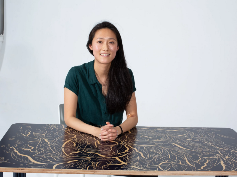 Chassie designer Ivy Tai sits atop one of her imaginative desk designs.