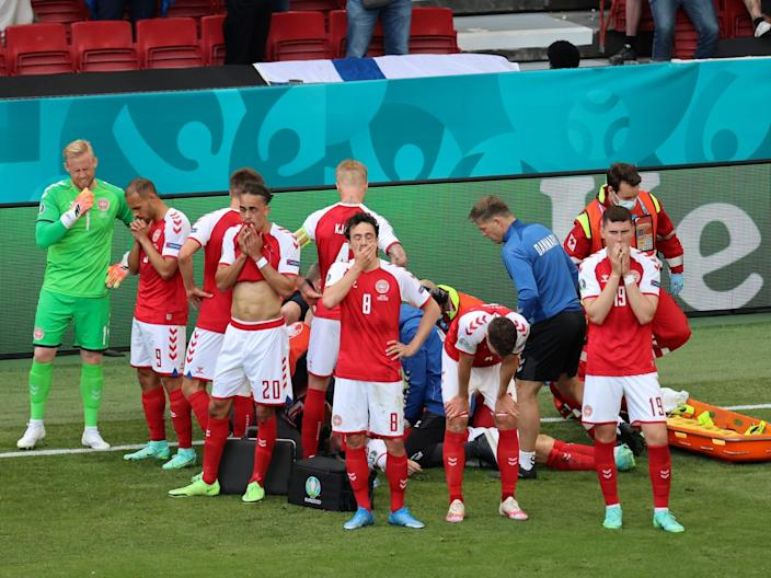 Denmark players surround Christian Eriksen as he receives medical treatment after collapsing on the field.
