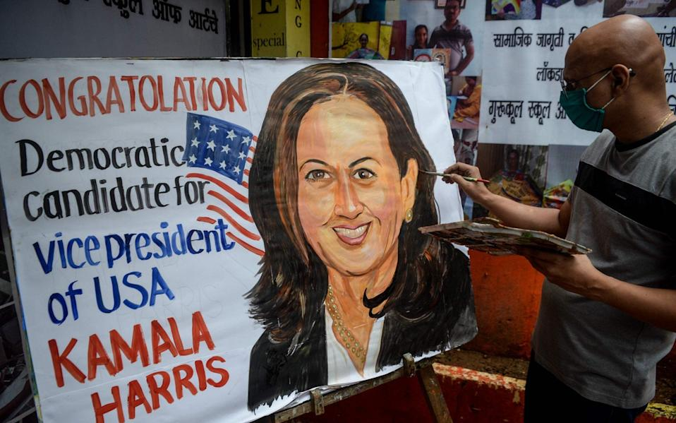 An art enthusiast paints on a canvas the face of presumptive US Democratic Vice President nominee Kamala Harris outside a drawing school in Mumbai  - AFP
