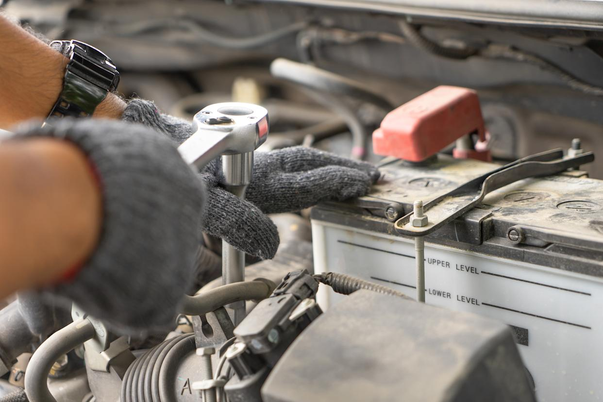 Mechanic, technician man check the car engine in garage. Car service, repair, fixing, checking maintenance working with socket wrench at workshop. Inspection vehicle concept Car mechanic using spanner examining automobile at repair service station.