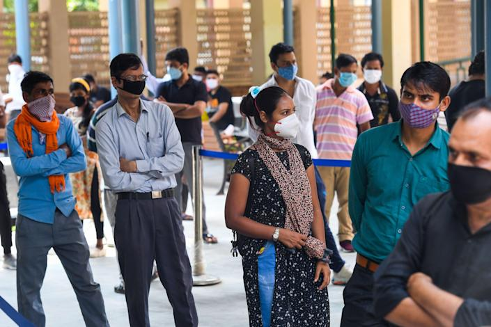 <p>People wait in a queue for Rapid Antigen Test (RAT) for the Covid-19 coronavirus at an ayurvedic dispensary in a residential area in New Delhi</p> (AFP via Getty Images)