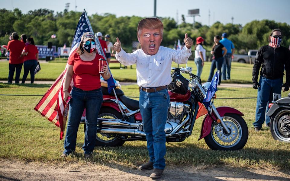 "An attendee wears a cutout mask in the likeness of U.S. President Donald Trump during a ""Trump Train"" rally in Laredo, Texas, U.S - Bloomberg"