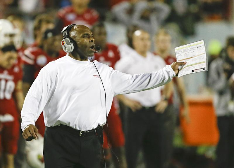 FILE - In this Dec. 28, 2013, file photo, Louisville head coach Charlie Strong calls out to players on the field during the second half of the Russell Athletic Bowl NCAA college football game against Miami in Orlando, Fla. Strong remains Louisville's football coach for the moment, telling assistants Saturday morning, Jan. 4, 2014, he hasn't decided to accept Texas' offer to become its coach. (AP Photo/John Raoux, File)