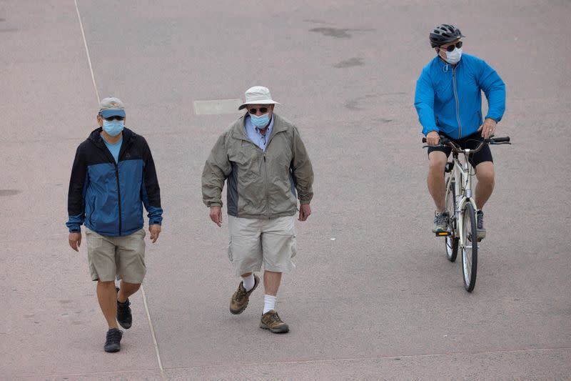 People wear face masks as they use the beach boardwalk during the outbreak of the coronavirus disease (COVID-19), in Huntington Beach, California